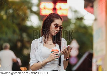 Woman Walks Down The Street With Coffee And Phone In Her Hands.
