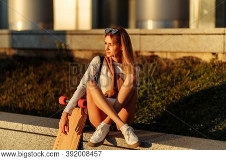 Skateboarding. The Blonde In A Lifestyle Style Rides A Longboard In The Summer Evening.