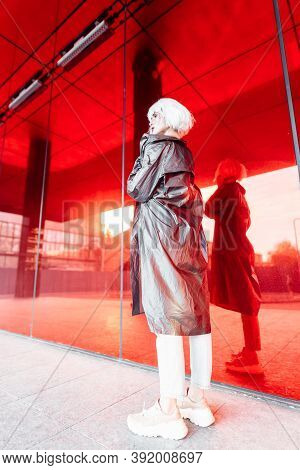 Fashion Blonde In A Futuristic Image On A Red Background.