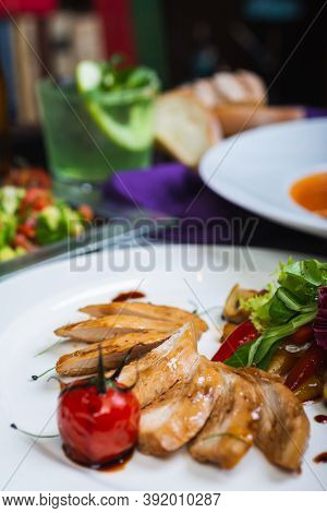 Baked Chicken Breast With Vegetables And Sun-dried Tomatoes On A Plate, Lunch Served For Guests On A