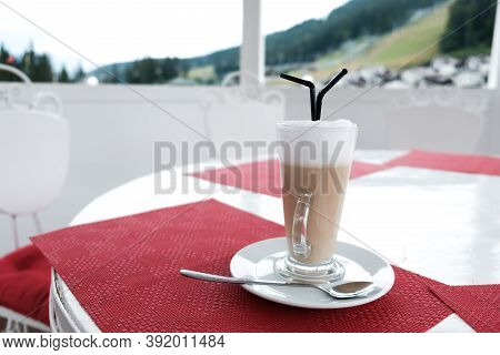 A Glass Cup Of Coffee Latte With Two Plastic Straws On A Table Outside. Serving Caffeinated Drinks I
