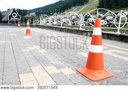 Orange Striped Road Cones On A Pavement. Safety Equipment For Traffic On A Street, Car Barricade Equ