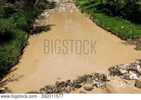 Dirty Polluted River In Ukraine. Unsanitary Undrinkable Water. Muddy Brown Water Color With Harmful
