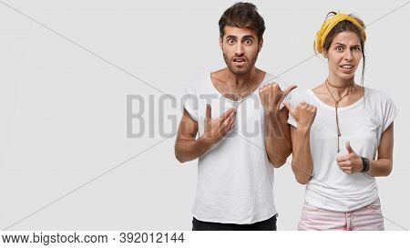 Puzzled Indignant Displeased Woman And Man Point At Each Other In Discontent, Dont Like Something, W