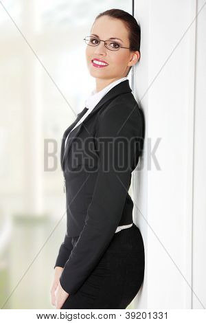 Portrait of successful happy businesswoman standing next to wall