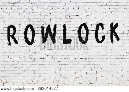 Inscription Rowlock Written With Black Paint On White Brick Wall.