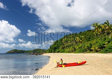 Young Woman With Red Sea Kayak On A Sandy Beach, Drawaqa Island, Yasawas, Fiji