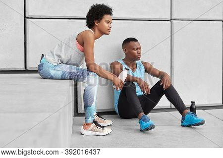 Photo Of Determined Woman And Man With Dark Skin, Healthy Body, Have Pensive Contemplative Facial Ex