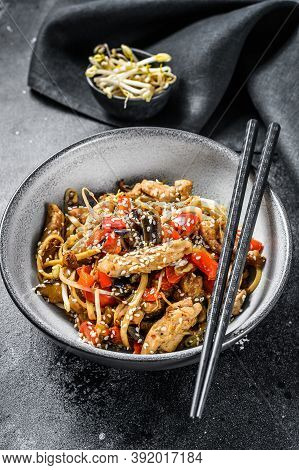 Udon Stir-fry Noodles With Chicken Meat And Sesame. Black Background. Top View