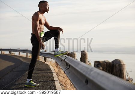 Panoramic View Of Determined Physically Active Young Man Stands Topless On Highway, Raises Leg On Ro