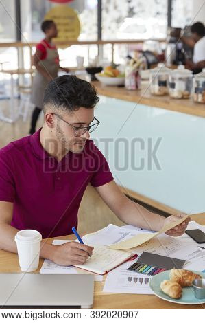 Vertical Shot Of Attractive Hipster Student Prepares Financial Project, Rewrites Information From Do