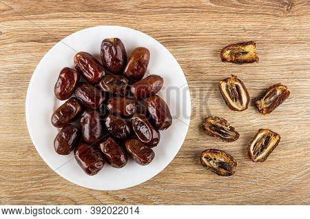 Dried Dates In Glass White Plate, Halves Of Dates With Seeds On Wooden Table. Top View
