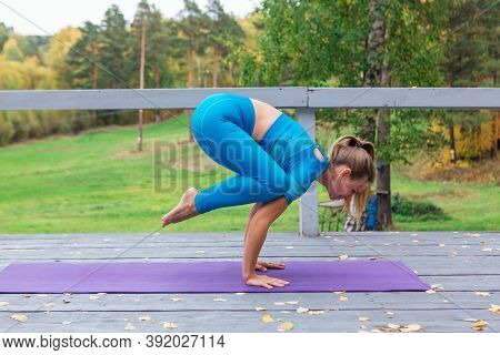 Young Woman Doing Yoga Exercises In Autumn Park.