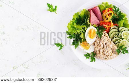 Breakfast Oatmeal Porridge With Boiled Egg, Ham And Vegetables Salad. Healthy Food. Top View, Overhe