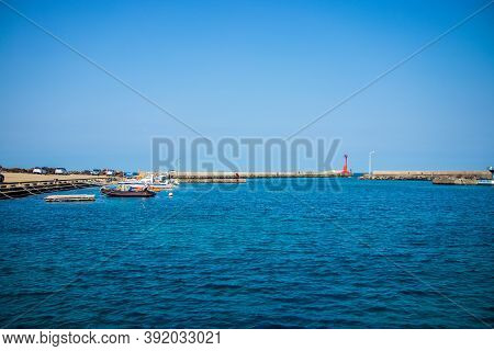 Jeju Island-march 2019: Blue Water At The Beach With Boat And Light House View