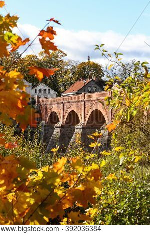 Sunny View With Old Brick Bridge Over River Venta. Photo Taken On A Warm Autumn Day, Yellow Leaves.