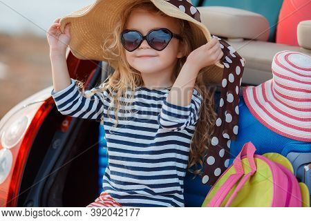 A 5-year-old Girl Is Sitting Alone In The Open Trunk Of A Red Car, Loaded With Things For Outdoor Ac