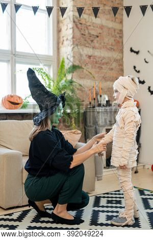 Young woman in witches costume crouching near armchair and adjusting bandages on boys costume in decorated room on Halloween