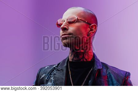 Stylish And Tattooed Rocker In Custom Leather Jacket With Collar And Glasses Poses Looking Away In B