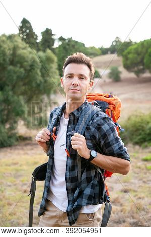 Portrait Of Pensive Male Traveler Standing On Nature And Looking At Camera. Handsome Caucasian Man T