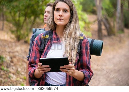 Serious Woman Checking Path Via Tablet And Walking On Mountainous Trail. Caucasian Hikers Or Travele