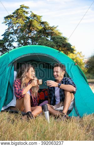 Cheerful Couple Sitting In Tent, Chatting And Drinking Tea. Happy Hikers Relaxing On Lawn, Camping A