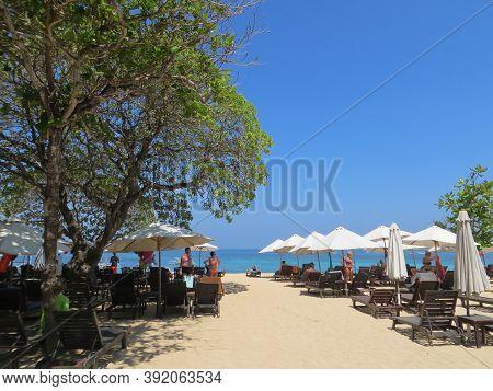 Badung Bali, Indonesia - October 3, 2019: People Getting Sun Bath On The Seaside Of Bengiat Beach Nu