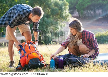 Beautiful Young Woman Looking At Man Unpacking Backpack. Two Travelers Camping On Grass Lawn Togethe