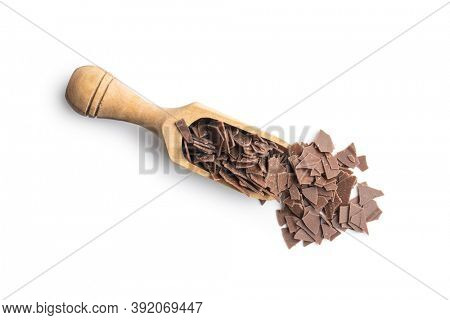 Grated dark chocolate in wooden scoop. Chocolate flakes isolated a on white background.