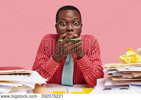 Mute Horrified Dark Skinned Young Man Covers Mouth With Hands, Has Bugged Eyes, Dressed Formally, Po