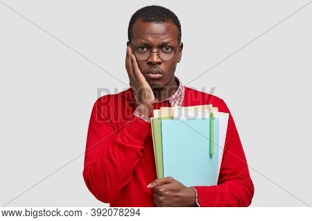 Cheerless Black Man Has Dejected Facial Expression, Keeps Hand On Cheek, Feels Tired Of Studying, Ho