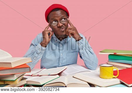 Contemplative Dark Skinned College Student Keeps Both Fingers On Temples, Purses Lips And Looks With