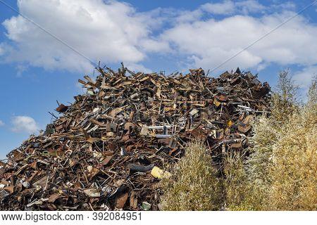 Scrap Metal Heap At Recycling Junkyard Against Blue Sky