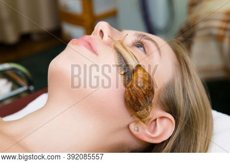 A Large Snail Akhatina Crawls On The Face Of A Young Woman And Rejuvenates Her Skin. The Concept Of