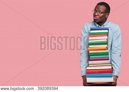 Image Of Dejected Black Man Looks With Miserable Expression Aside, Holds Pile Of Books, Dressed In F