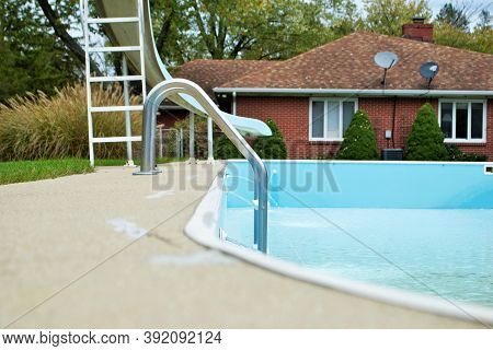 Backyard Swimming Pool With Pool Slide And Ladder Emptied Out Shutting Down For Winter
