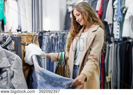 Pretty Elegant Woman Shopping In Clothes Store. Girl Choosing, Looking And Shopping Trendy Clothes.