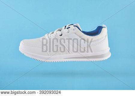 White Sports Sneakers Levitate On A Blue Background. Stylish Man Sneakers For Fitness. White Sneaker