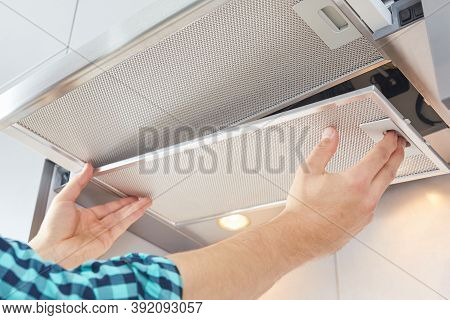 Mans Hands Removing A Filter From Cooker Hood For Cleaning Or Service. Replacing Filter In Kitchen H