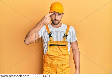 Young handsome man wearing handyman uniform over yellow background pointing unhappy to pimple on forehead, ugly infection of blackhead. acne and skin problem