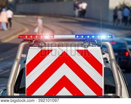 A Police Patrol Pickup Truck With A Flasher And A Striped Warning Sign In The Back On A City Street