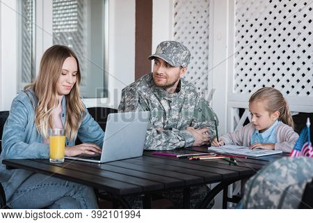 Military Serviceman Looking At Woman Typing On Laptop And Sitting Near Girl Drawing With Colorful Pe