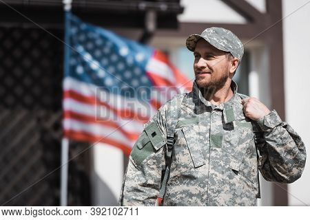 Military Veteran In Camouflage Looking Away With Blurred American Flag On Background