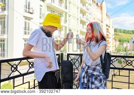 Cheerful Talking Students Teenagers Guy And Girl In City Drinking Milk Yogurt From Bottle. Lifestyle