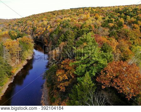 The Aerial View Of The Striking Colors Of Fall Foliage By The River Near Tunkhannock, Pennsylvania,