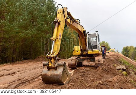 Excavator During Construction New Road In Forest Area. Yellow Backhoe At Groundwork. Earth-moving Eq