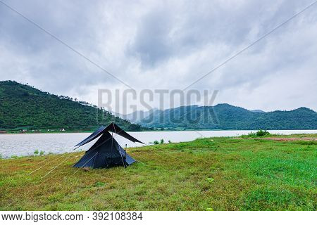 Nature Tourism Concept With Black Tent By The Lake, There Are Valleys And Clouds In The Rainy Season