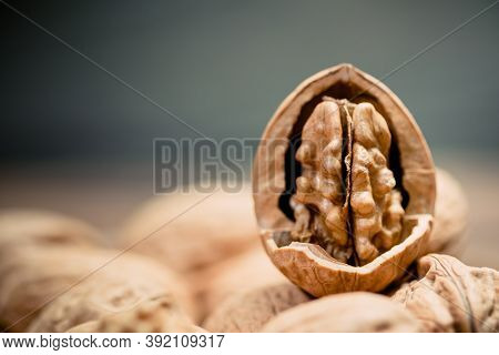 Still Life With Walnut Kernels And Whole Walnuts On Rustic Old Wooden Table