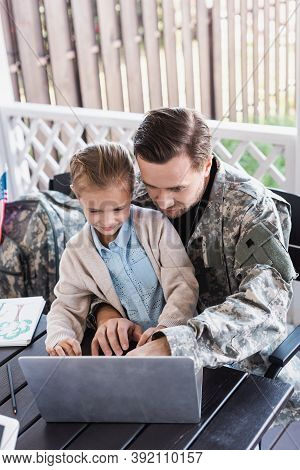 Military Serviceman Hugging Girl And Looking At Laptop, While Sitting At Table, Stock Image