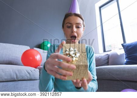 Caucasian woman at home celebrating birthday, in living room wearing party hat, gasping in surprise and opening a present. Social distancing during Covid 19 Coronavirus quarantine lockdown.